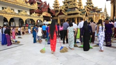 Pilgrims in a ceremony with brooms at the Shwedagon Pagoda. Yangon, Myanmar Stock Footage