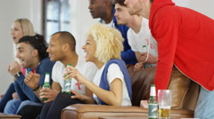 4K Excited group of friends watching sports game on TV celebrate when team score - stock footage