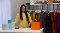 Young Woman Takes a Clothes Folds Puts Into Bag Client Brunette Woman is Buying - stock footage