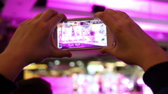 Spectators hands holding shooting video via smartphone of a concert performance - stock footage