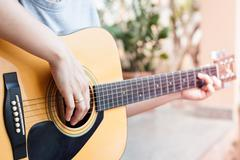 Woman's hands playing acoustic guitar - stock photo