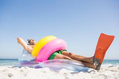 Man lying on lilo wearing rubber ring - stock photo