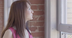 Slow-motion pretty Asian girl stands by windows in urban hallway 4K Stock Footage