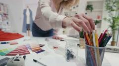 4K Fashion designer working at her desk in creative studio Stock Footage