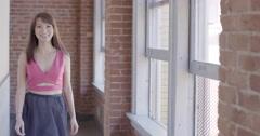 Slow-motion pretty Asian girl approaching in urban hallway 4K Stock Footage