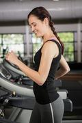 Happy woman jogging on treadmill - stock photo