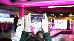 Girl hands holding shooting video via smartphone of a concert performance Stock Footage