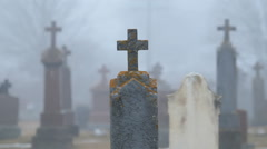 Moss covered cross on gravestone in misty graveyard. - stock footage