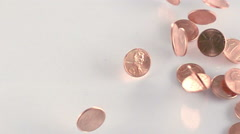 Ultra slo mo pennies drop on glass white background high angle Stock Footage