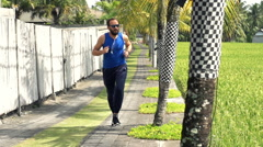 Young man jogging on path in country Stock Footage