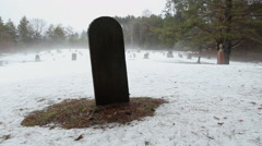 Old gravestone in misty snow covered cemetery. - stock footage