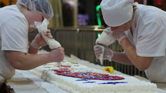 Cookery hands of culinary experts squeeze the cream on a big white cake Stock Footage