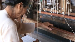 Textile manufacture in craft village where women work on weaving loom machine Stock Footage