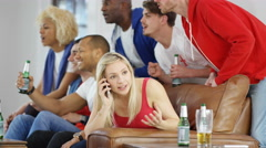 4K Woman talking on mobile phone while rowdy friends watch sports game on TV Stock Footage