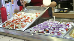 Big mall foodcourt food market a seller lays out large salad pan Stock Footage