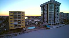 Jib type shot of condos on beach at sunrise Stock Footage