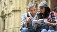 Couple of tourists looking at city guide - stock footage