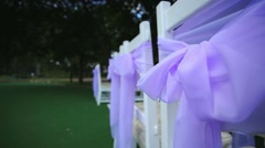 Wedding decor on the chairs, ribbons on white chairs, satin ribbons. - stock footage