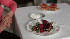 Female hand takes a fresh juicy strawberries, dipped it in yogurt. Close-up Stock Footage
