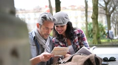 Couple of tourists in town looking at city guide - stock footage