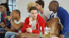 4K Man talking on mobile phone while rowdy friends watch sports game on TV - stock footage