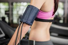 Mid section of woman exercising on treadmill with mobile on armband - stock photo