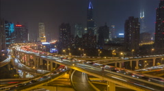 Traffic flows past the skyline of Shanghai city, night time lapse, urban China - stock footage