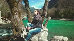 Romantic brunette sitting on the rock by the river, looking around in sunny day. Stock Footage