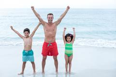 Father and children standing with arms raised at beach - stock photo