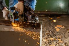 Worker working of a grinding machine - stock photo