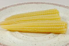 Small loaded corns on plate, yellow, health - stock photo