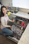 Portrait of woman arranging plates in dish washer - stock photo