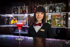 Bartender girl at night club counter offering coctail barmaid Kuvituskuvat