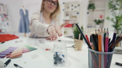 4K Fashion designer working at her desk in creative studio - stock footage