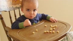 An adorable baby boy eating cereal in his highchair Stock Footage