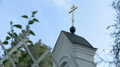 View of cross on church and lilac bush by fence - stock footage