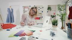 4K Fashion designer working at her desk in creative studio - stock footage
