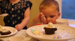 Children eating cupcakes for birthday party celebration - stock footage