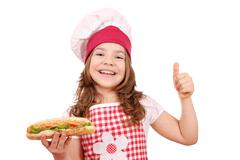 Happy little girl with hot dog and thumb up Stock Photos