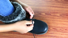 Close up of a little girl tying his winter boots. Stock Footage