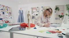 4K Portrait of smiling fashion designer working at her desk in creative studio - stock footage