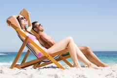 Couple relaxing on deck chair Stock Photos