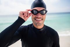 Young man in wetsuit and swimming goggles standing on beach - stock photo