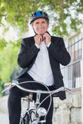 Portrait of businessman adjusting helmet Stock Photos