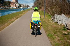 cyclist wearing a fluorescent jacket rolling bicycle on a bike path in border - stock photo