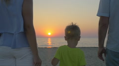 Family with child looking at sunset over sea - stock footage