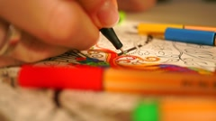 Young woman coloring some black and white drawing. Macro shot Stock Footage