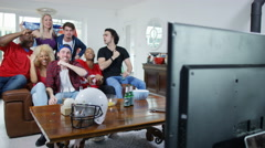 4K Friends watching American football game on TV celebrate when team scores - stock footage