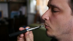 Man smokes electronic cigarette at home exhaling smoke Stock Footage