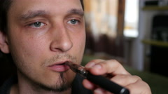 Man smokes electronic cigarette at home exhaling smoke face closeup Stock Footage